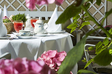 Breakfast terrace in the green inner courtyard of the Hotel Admiral, Munich